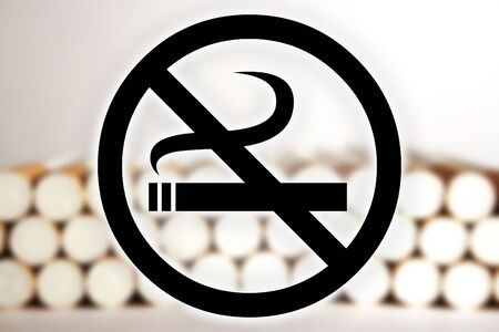 public works: Black no smoking sign in front of a blurry picture of cigarettes.