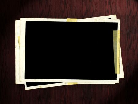 Blank picture frames on dark wooden table.