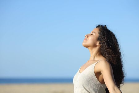Side view portrait of a relaxed latin girl breathing deeply fresh air on the beach a sunny day Standard-Bild