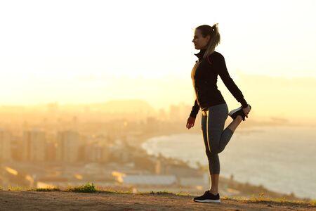 Seitenansicht Ganzkörperporträt einer Läuferin, die bei Sonnenuntergang das Bein in den Außenbezirken der Stadt streckt Standard-Bild