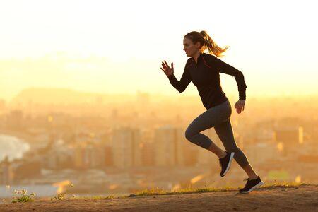 Seitenansicht Ganzkörperporträt einer Läuferin, die bei Sonnenuntergang am Stadtrand der Stadt läuft Standard-Bild