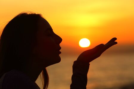 Profile of a woman silhouette blowing or kissing sun at sunset on the beach