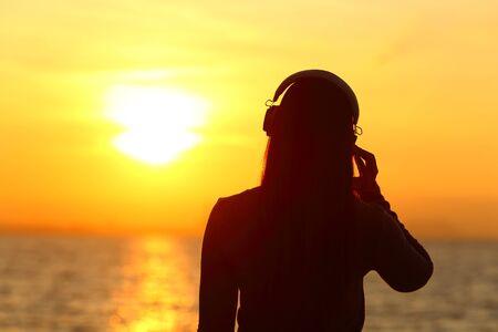 Silhouet van een meisje met een koptelefoon op die naar muziek luistert bij zonsondergang op het strand Stockfoto