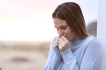 Verdrietig meisje klaagt alleen staande op het strand Stockfoto