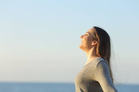 Profile of a happy woman breathing fresh air and heating on the beach at sunset Standard-Bild