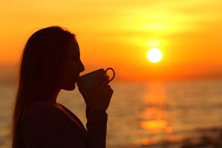 Zijaanzichtportret van een vrouwensilhouet dat koffie drinkt bij zonsopgang op het strand Stockfoto