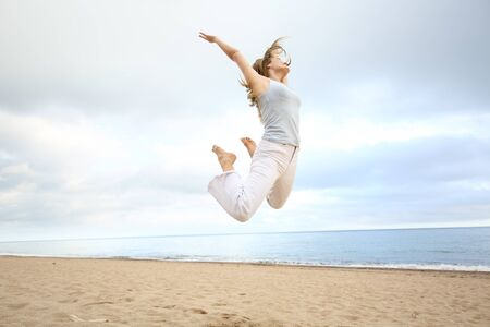 Full body portrait of an excited happy woman jumping on the beach Stock Photo