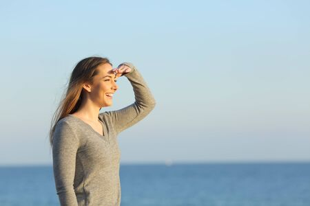 Happy woman searching looking at horizon on the beach with hand on forehead Stockfoto