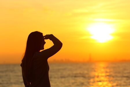 Silhouette of a woman searching with hand on forehead at sunset on the beach Stock Photo