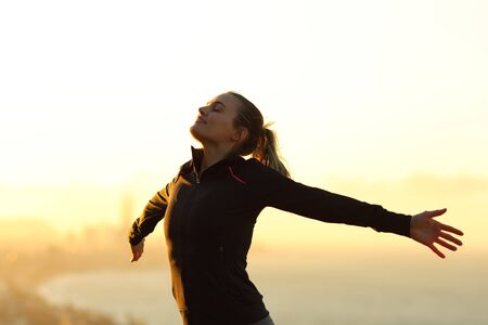 Happy runner breathing fresh air outstretching arms at sunset in the city outskirts