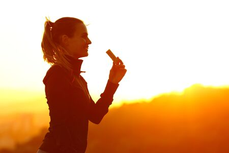 Silhouette of runner woman eating energy bar after running at sunset in the mountain