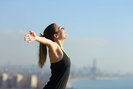 Side view portrait of an excited runner celebrating success outdoors in a city outskirts