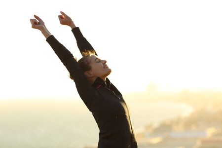 Excited runner raising arms celebrating achievement outdoors at sunset in city outskirts