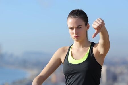 Angry sportswoman gesturing thumbs down in city outskirts