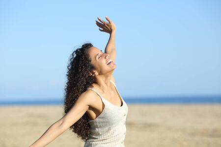 Happy latin woman laughing imitating flight outstretching arms on the beach 版權商用圖片