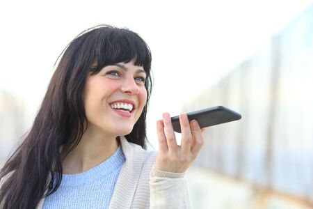 Happy woman recording message using voice recognition on smart phone in a bridge