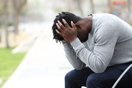 Side view portrait of a sad depressed black man sitting on a bench in a park Banque d'images