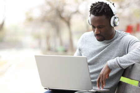 Black man wearing headphones e-learning using laptop sitting on a bench in a park