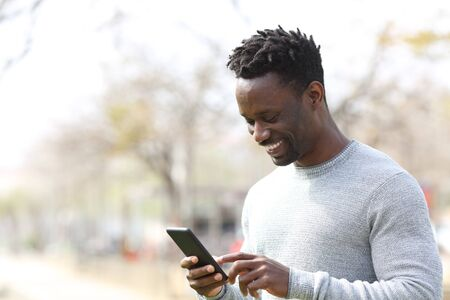 Happy black man using smart phone walking in a park a sunny day