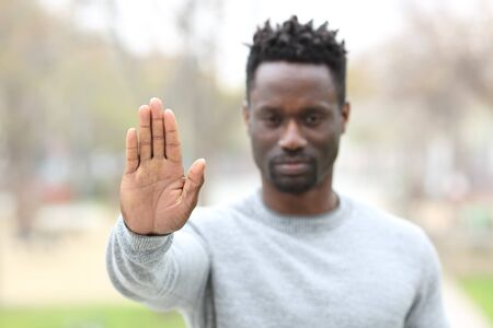 Front view portrait of an angry black man gesturing stop showing hand palm outdoors in a park Imagens