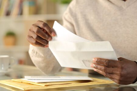 Close up of black man hands putting a letter inside an envelope on a desk at home