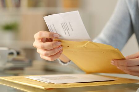 Close up of woman hands opening a letter on a padded envelope on a desk at home Archivio Fotografico