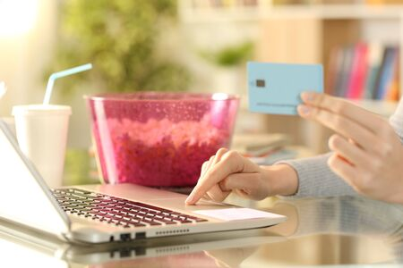 Close up of girl hands paying media content service with credit card and laptop on a desk at home