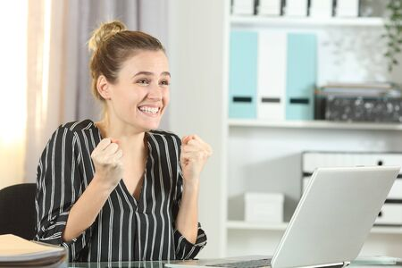 Excited entrepreneur celebrating good news on laptop stting on a desk in the office