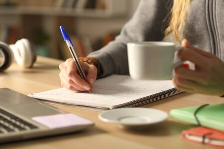 Close up of student girl hands holding coffee cup writing on notebook at night sitting on a desk at home