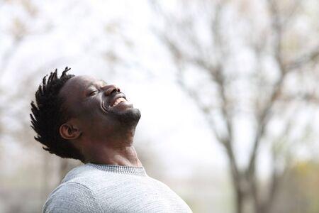 Happy black man breathing fresh air outdoors in winter standing in a park Foto de archivo