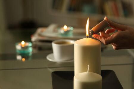 Close up of woman hand lighting candles with lighter in the night at home on a power outage
