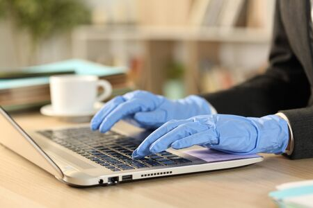 Close up of freelance woman hands with defective latex gloves working on laptop preventing contagion sitting on a desk at the office