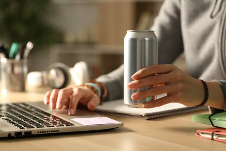 Close up of student girl hands holding energy drink can at night studying on a desk at home