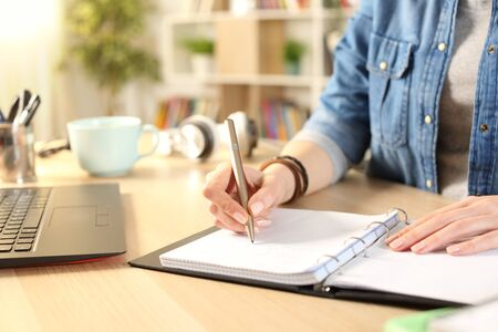 Close up of student girl hand writing on notebook on a desk at home