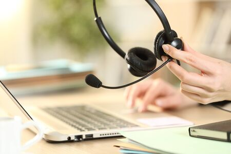 Close up of telemarketer holding headset working on laptop on a desk at home office