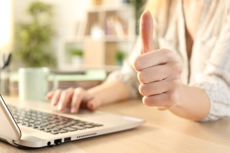Close up of woman hands using laptop with thumbs up sitting on a desk at home