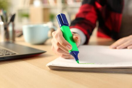 Close up of student girl hands using green highlighter pen on notebook on a desk at home