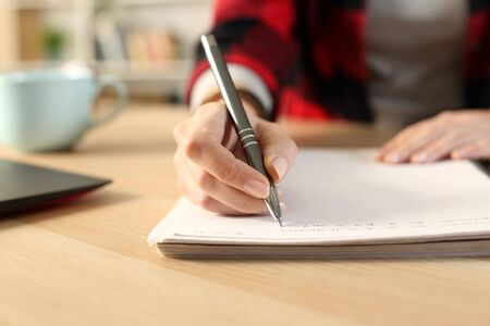 Close up of student girl hands writing notes on notebook at home sitting on a desk Imagens