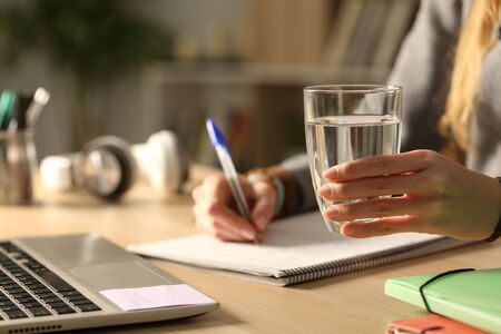 Close up of student girl hands holding glass of water at night studying siting on a desk Imagens