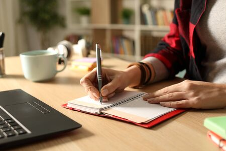 Close up of student girl hand writing on agenda on a desk at home in the night Imagens