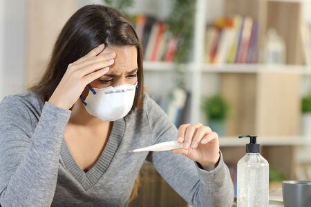 Worried woman wearing protective mask with covid-19 fever symptoms looking at thermometer sitting on a desk at home
