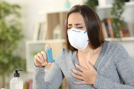 Woman with coronavirus symptoms wearing protective mask holding inhaler suffocating touching chest at home