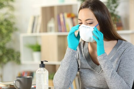 Woman putting protective mask due coronavirus with gloves sitting on a desk at home