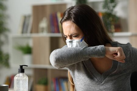 Sick woman with mask coughing on elbow due coronavirus infection at home in the night Stock Photo
