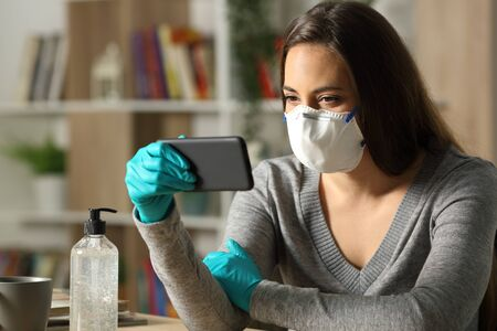 Woman watching video on smart phone on coronavirus confinement itting on a desk in the night at home