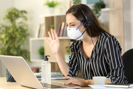Telemarketer woman greeting on videocall with laptop sitting on a desk at homeoffice on coronavirus confinement