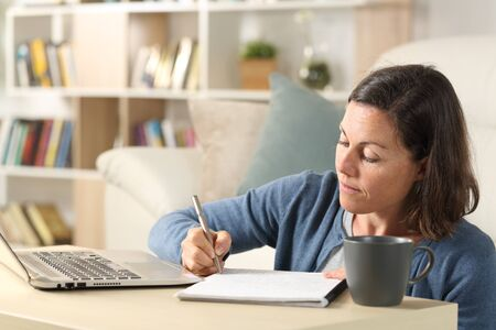Adult woman with laptop writing notes on notebook sitting on the floor on a coffee table at home Banco de Imagens