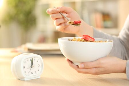 Close up of woman hands eating cereal bowl with fruit after intermittent fasting sitting on a table at home