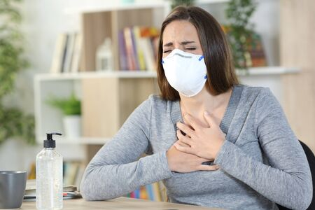 Sick woman of coronavirus with protective mask suffocating holding chest sitting at home