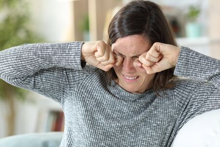 Middle age woman scratching itchy eyes sitting on a couch at home
